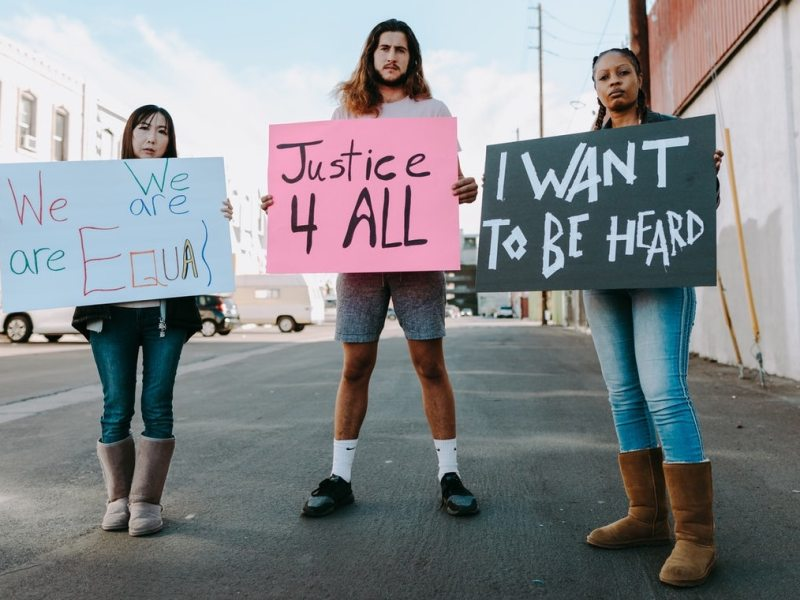 """Three people are standing in street and holding handmade signs stating """"We are all equal"""", """"Justice 4 All"""", and """"I want to be heard."""""""