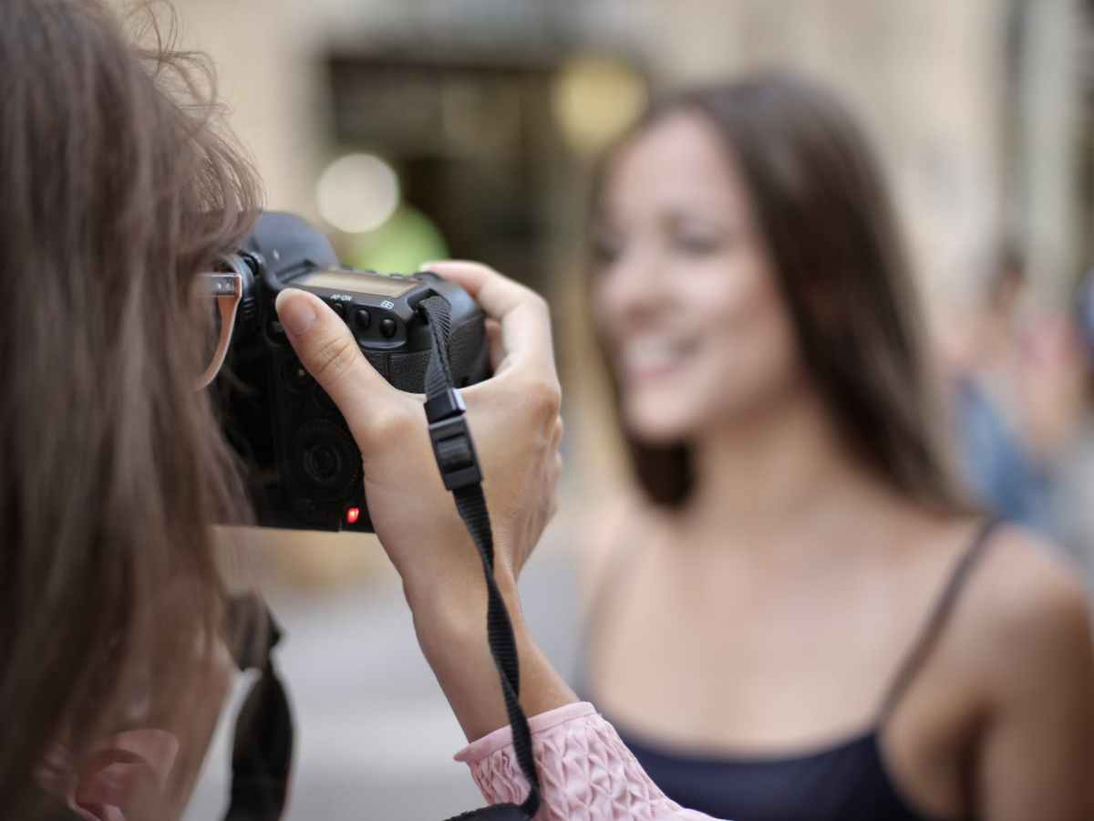 Looking over the shoulder of a photographer as they take a picture of another person who is blurred due to the distance.